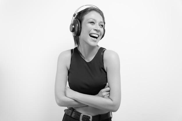 Portret roześmianej kobiety w słuchawkach. koncepcja akcesoriów muzycznych. różne środki przekazu