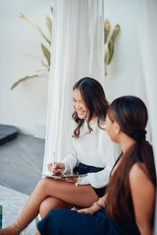 Portret roześmianej kobiety z tabletem, która pracuje razem ze swoim asystentem siedzącym na progu rezydencji na zewnątrz.