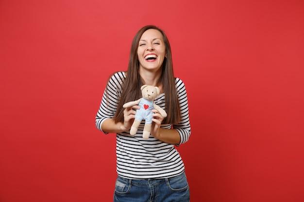 Portret roześmianej ładnej młodej kobiety w swobodnych ubraniach w paski, trzymającej pluszową zabawkę pluszowego misia