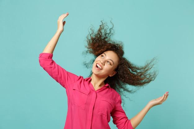 Portret roześmiany ładna afrykańska dziewczyna w ubranie skoki z latającymi włosami na białym tle na tle niebieskiej ściany turkus w studio. koncepcja życia szczere emocje ludzi. makieta miejsca na kopię.