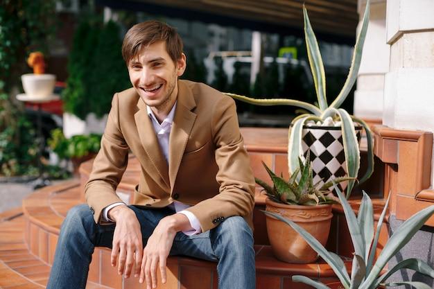 Portret roześmiany młody zrelaksowany mężczyzna siedzi na zewnątrz na zabytkowe okrągłe schody