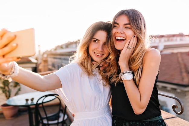 Portret roześmianych przyjaciół, ciesząc się razem weekend i robiąc selfie na miasto rano