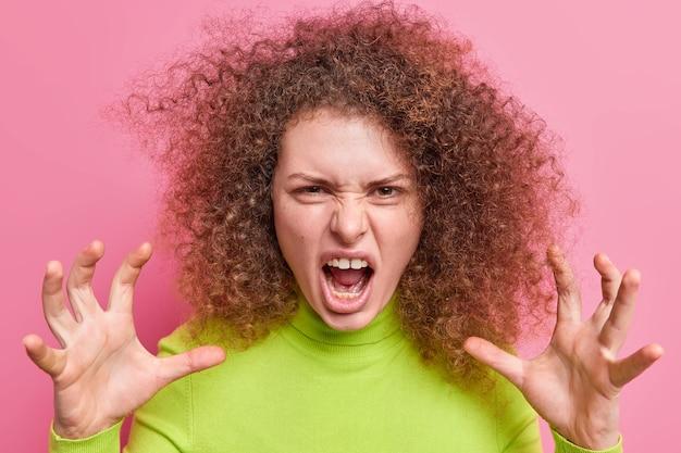 Portret rozgniewanej kobiety marszczy brwi, wykrzykuje zirytowany, sprawia, że pazury samochodu trzyma szeroko otwarte usta ma kręcone, krzaczaste włosy, nosi zielony golf, wyraża negatywne emocje pozy w pomieszczeniach. koncepcja gniewu