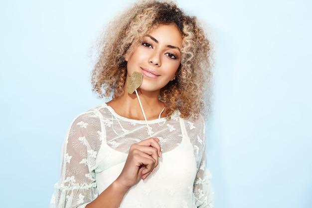 Portret rozkosznej uroczej kobiety z blond afrykańską fryzurę z dużymi ustami na patyku.