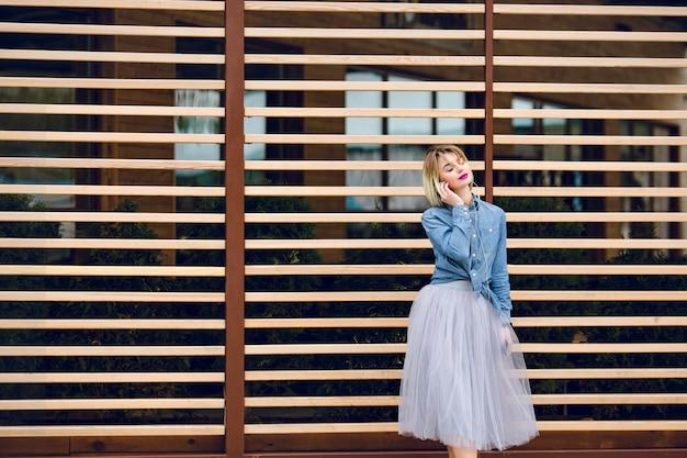 Portret rozmarzonej dziewczyny z latającymi krótkimi blond włosami i jasnoróżowymi ustami, słuchająca muzyki na smartfonie z pasiastymi drewnianymi belkami za