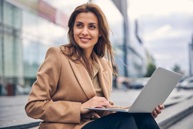 Portret rozmarzonej freelancerki z komputerem na kolanach, patrzącą w dal