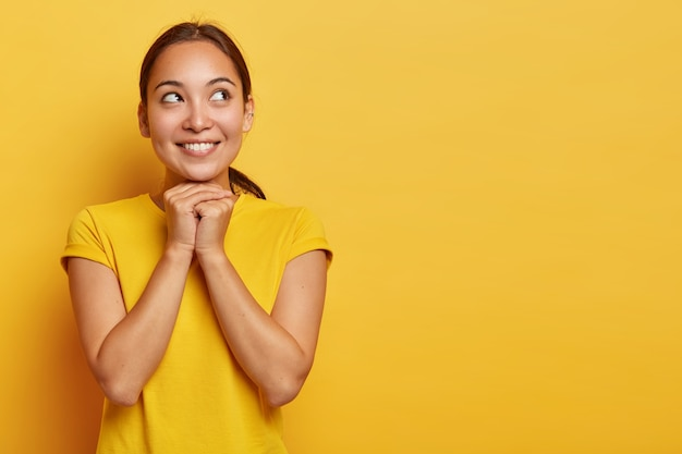 Portret rozmarzonej, zadowolonej etnicznej dziewczyny skupionej na boku ze szczęśliwym uśmiechem, trzyma ręce pod brodą, patrzy z nadzieją, wierzy w lepsze, nosi swobodną żółtą koszulkę, stoi w