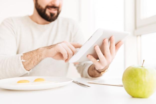 Portret rozmyty dorosły mężczyzna w przypadkowej koszula ma zdrowego posiłek z smażyć jajka w mieszkaniu, podczas gdy używać cyfrową pastylkę