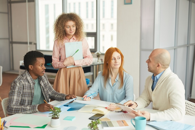 Portret różnorodnego zespołu biznesowego współpracującego nad kreatywnym projektem w nowoczesnym białym biurze, kopia przestrzeń