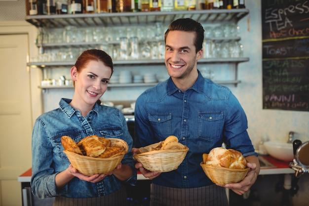 Portret rozochoceni baristas oferuje chleby przy sklep z kawą