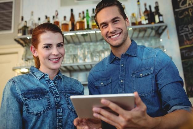 Portret rozochoceni baristas z cyfrową pastylką przy kawiarnią