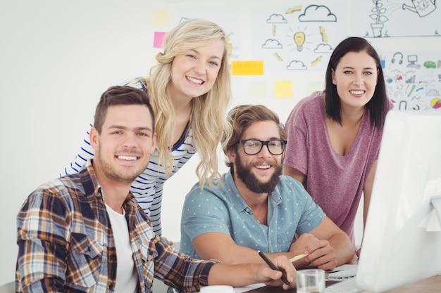 Portret rozochoceni biznesowi profesjonaliści pracuje przy komputerowym biurkiem w kreatywnie biurze