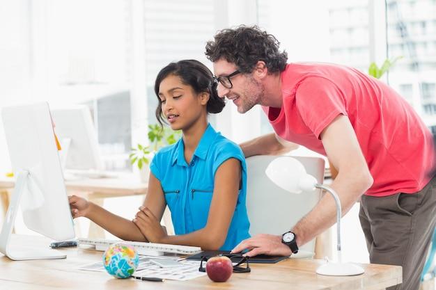 Portret rozochoceni koledzy używa komputer