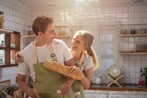 Portret rozochoceni pozytywni caucasian młodzi partnery używa naczynia i warzywa walczy w nowożytnej białej kuchennej pobliskiej stołowej kuchence ma wakacje wydaje czas salowy wpólnie.