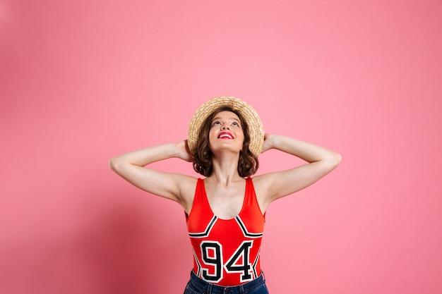 Portret rozochocona dziewczyna jest ubranym swimsuit i słomianego kapelusz