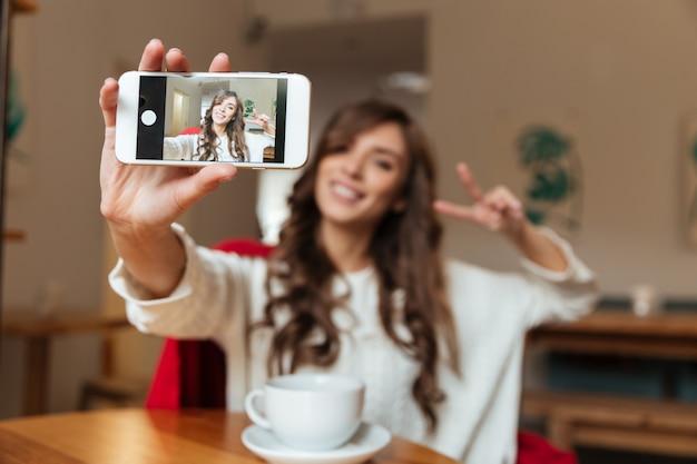Portret rozochocona kobieta bierze selfie