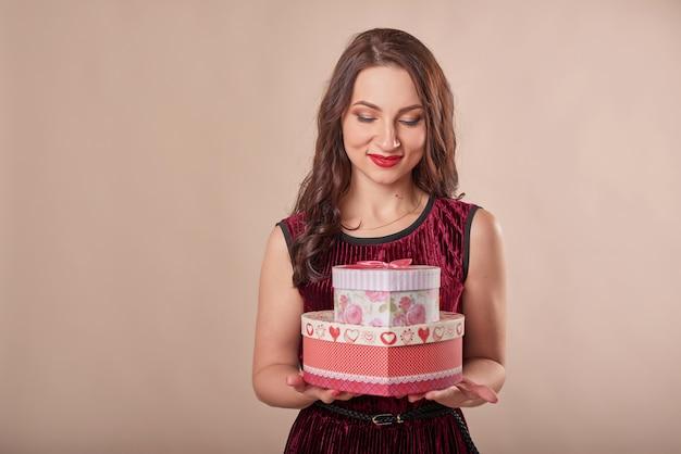 Portret rozochocona kobieta w czerwieni sukni mienia prezenta pudełkach