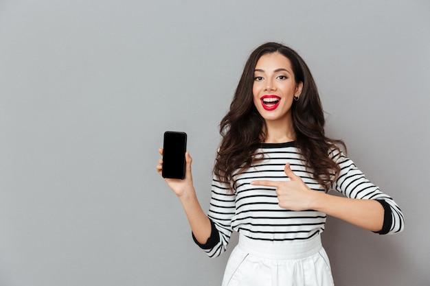 Portret rozochocona kobieta wskazuje palec