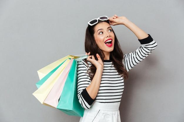 Portret rozochocona kobiety mienia torba na zakupy