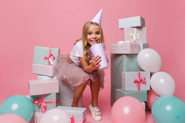 Portret rozochocona mała dziewczynka w urodzinowym kapeluszu