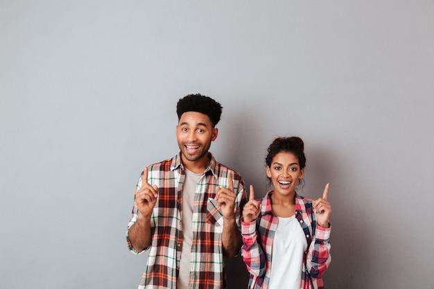 Portret rozochocona młoda afrykańska para wskazuje up z palcami