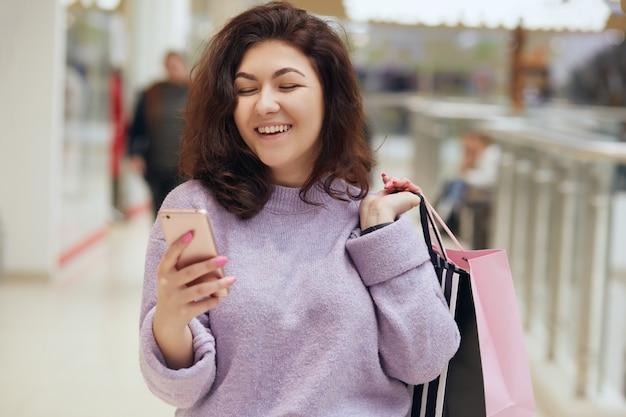 Portret rozochocona młoda dama z falistym włosianym mienie telefonem komórkowym w ręce, patrzejący swój ekran z szczęśliwym wyrazem twarzy, kobiety mienia torba na zakupy.