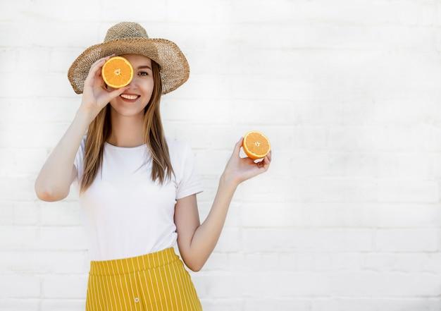 Portret rozochocona młoda dziewczyna trzyma kapelusz w dwa plasterkach pomarańcze na biel ścianie