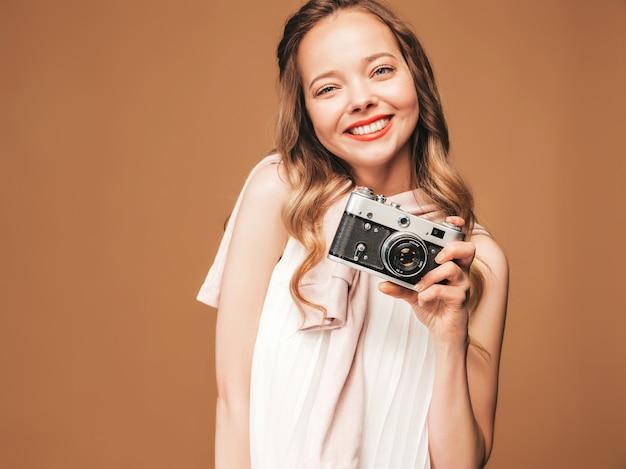 Portret rozochocona młoda kobieta bierze fotografię z inspiracją i jest ubranym biel suknię. dziewczyna trzyma aparat retro. pozowanie modelu