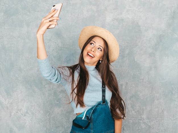 Portret rozochocona młoda kobieta bierze fotografii selfie i jest ubranym nowożytnych ubrania i kapelusz.