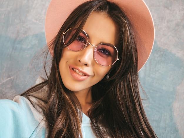 Portret rozochocona młoda kobieta bierze fotografii selfie z inspiracją i jest ubranym nowożytnych ubrania i kapelusz.