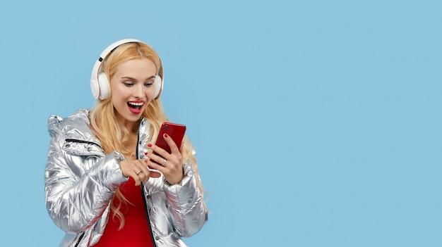 Portret rozochocona młoda kobieta jest ubranym przypadkową srebną kurtkę odizolowywającą, słucha muzyka z hełmofonami, tanczy. wow i zaskoczona twarz