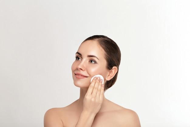 Portret rozochocona młoda kobieta usuwa twarz makijaż z wacikiem