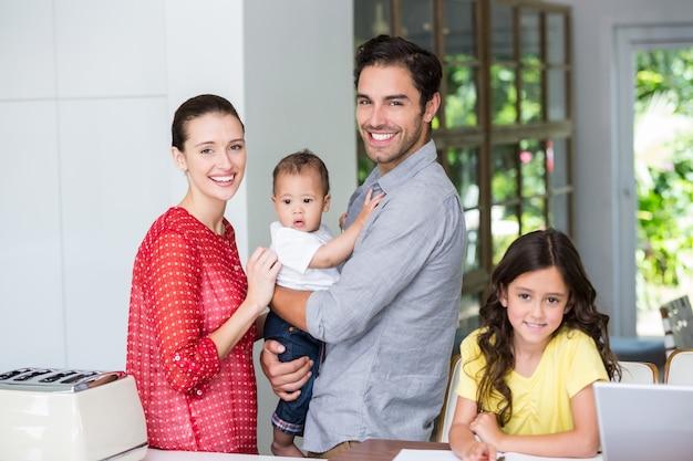 Portret rozochocona rodzina przy biurkiem