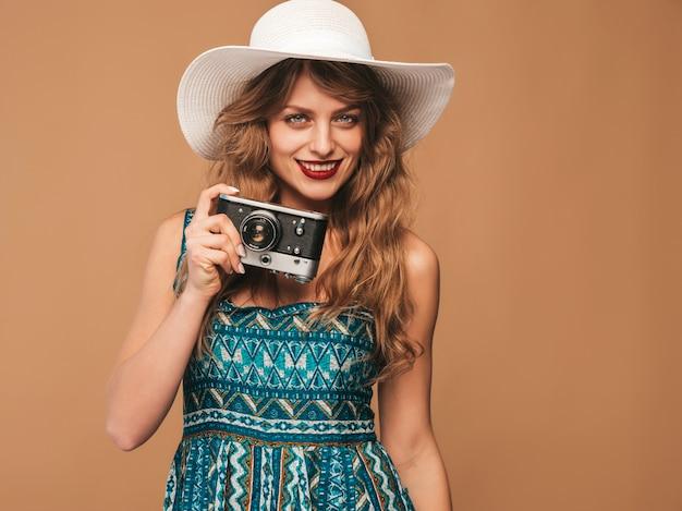 Portret rozochocona uśmiechnięta młoda kobieta bierze fotografię z inspiracją i jest ubranym lato suknię. dziewczyna trzyma aparat retro. modelu pozowanie w kapeluszu