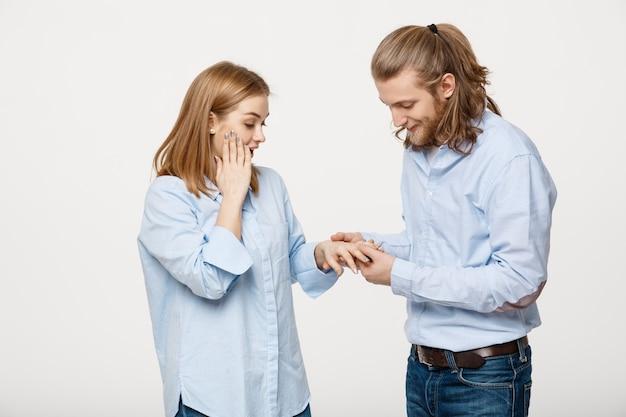 Portret rozochocona zadowolona przystojna mężczyzna jest ubranym pierścionek zaręczynowego dla jej dziewczyny
