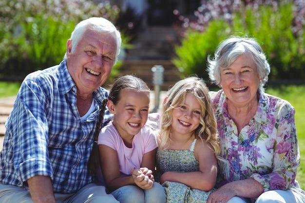 Portret rozochocone dziewczyny z dziadkami podczas gdy siedzący w podwórku