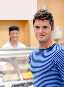 Portret rozochocony mężczyzna wybiera jego lunch w bufecie