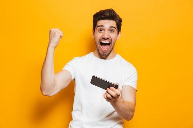 Portret rozochocony młody człowiek bawić się gry na telefonie komórkowym odizolowywającym nad żółtym tłem, świętuje