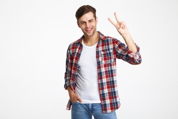 Portret rozochocony młody człowiek pokazuje pokoju gest