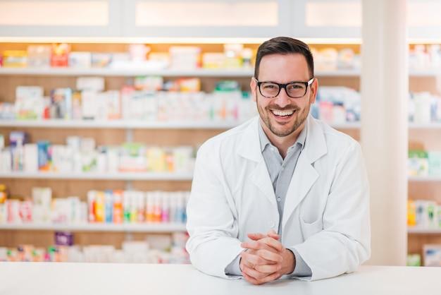 Portret rozochocony przystojny farmaceuta opiera na kontuarze przy apteką.