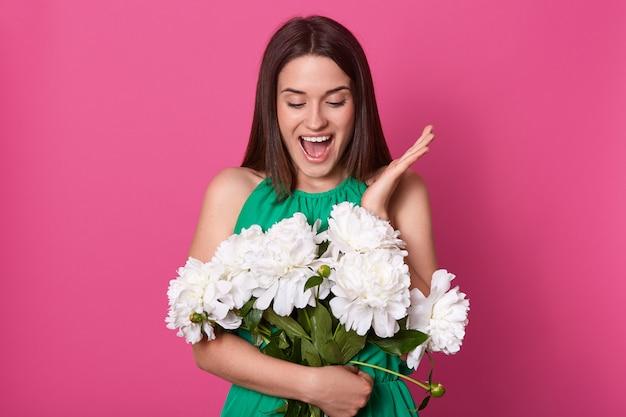 Portret rozochocony szczęśliwy młodej kobiety mienia bukiet białe peonie