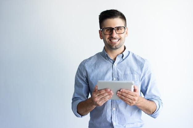Portret rozochocony z podnieceniem pastylka użytkownik jest ubranym eyeglasses