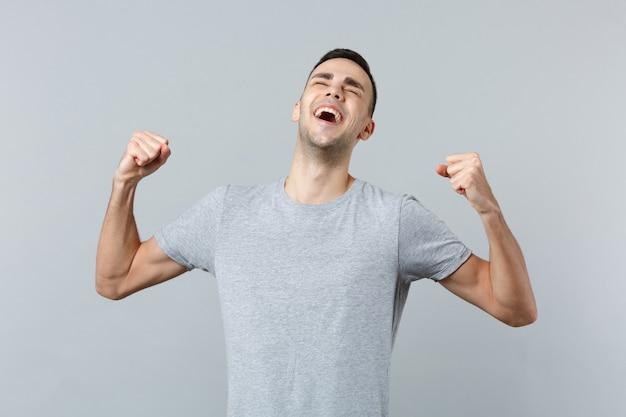 Portret rozradowanego, szczęśliwego, śmiejącego się młodego mężczyzny w zwykłych ubraniach, zaciskającego pięści jak zwycięzca