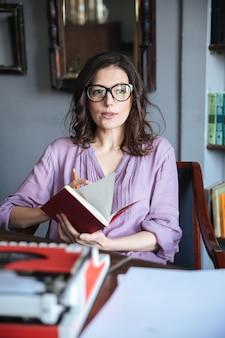 Portret rozważna dojrzała kobieta trzyma notatnika w eyeglasses
