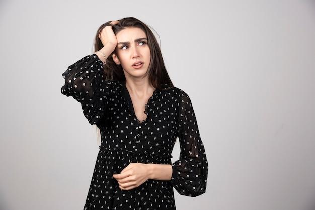 Portret rozważna dziewczyna trzymając się za ręce na głowie.