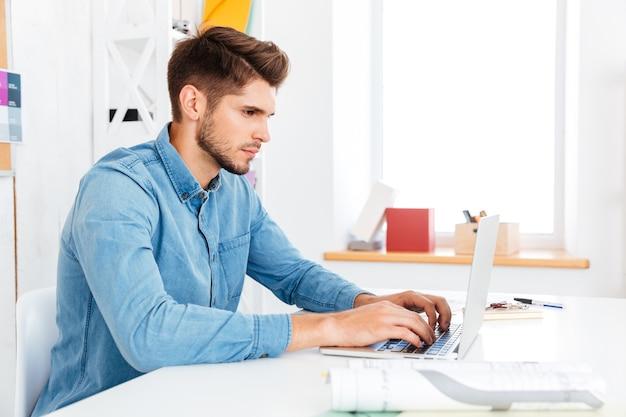 Portret rozważnego młodego biznesmena siedzącego przy biurku i korzystającego z laptopa w biurze