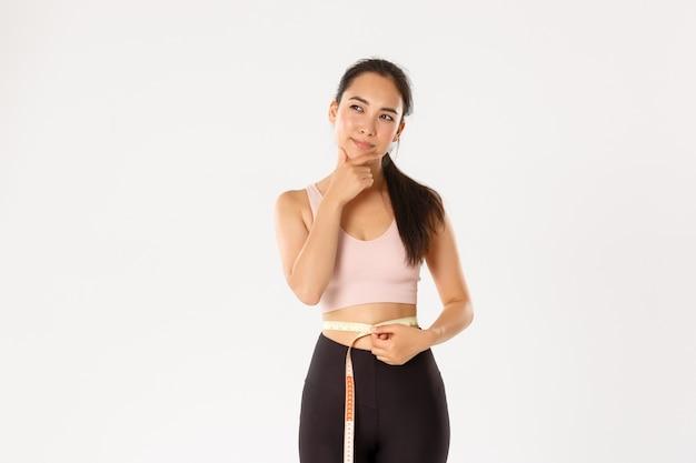 Portret rozważnej azjatyckiej trenerki siłowni, sportsmenka myśli o utracie wagi, mierzenie talii po treningu, białe tło.