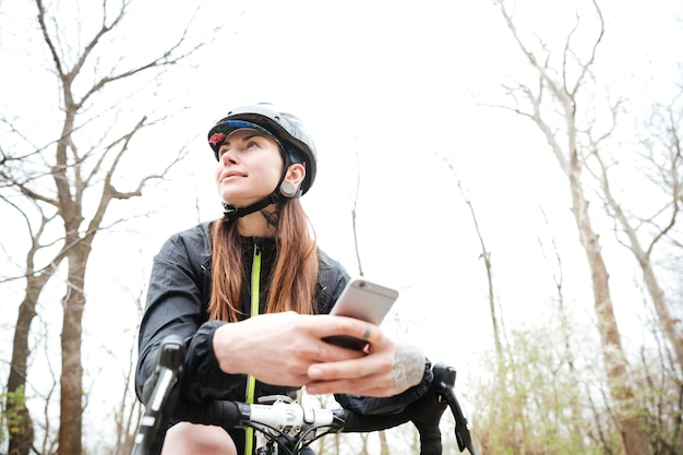 Portret rozważnej młodej kobiety na rowerze z telefonem komórkowym w parku