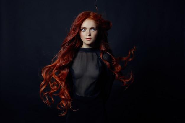 Portret rude sexy kobieta z długimi włosami na czarnym tle. idealna dziewczyna o niebieskich oczach, ładnej czystej skórze, pięknym naturalnym makijażu, rudych włosach