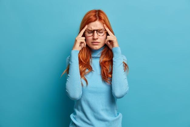 Portret rudej, młodej europejki cierpiącej na silny ból głowy, trzyma palce wskazujące na skroniach, stara się skoncentrować i kontynuuje pracę ubrana w luźny strój.